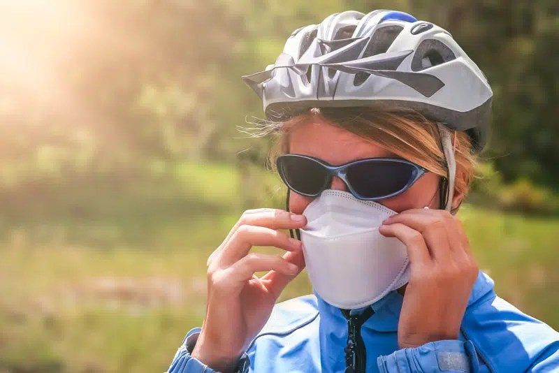 Cyclist putting on a protective mask