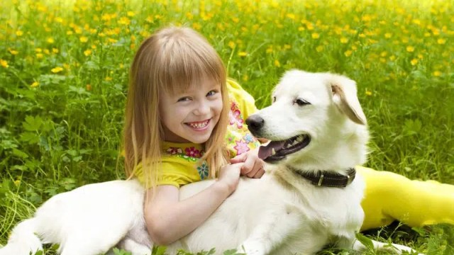 young girl laying with a dog in the grass