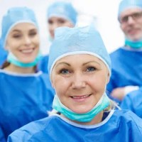 Smiling healthcare workers wearing medical gowns and face masks.