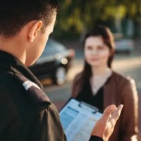 Police officer looking at clipboard asking woman questions