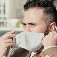 man putting on a mask outdoors