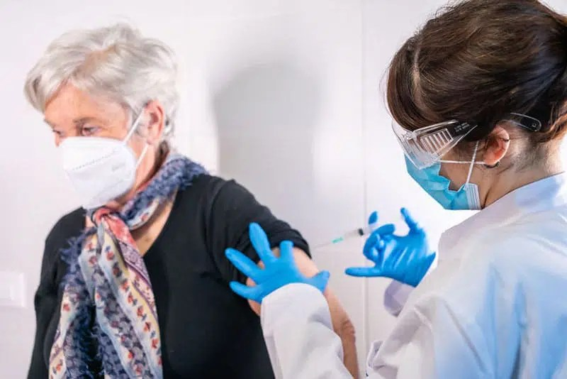 senior woman receiving the injection of the coronavirus vaccine by a doctor