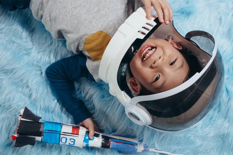 young boy dressing in a toy space helmet holding a toy rocket