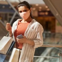 woman at a mall carrying shopping bags wearing a medical mask