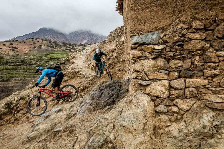 Riding steep MTB trails out of villages on the Mountain bike tour Morocco, Africa