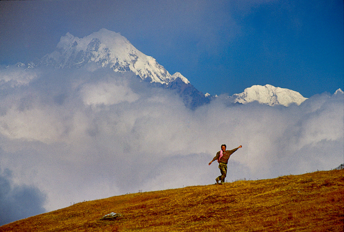Chhiri Sherpa sings and dances on a high ridge beneath Mt. Langtang Lirung. Bagmati District, Nepal, 1994. Photo by Pat Morrow.