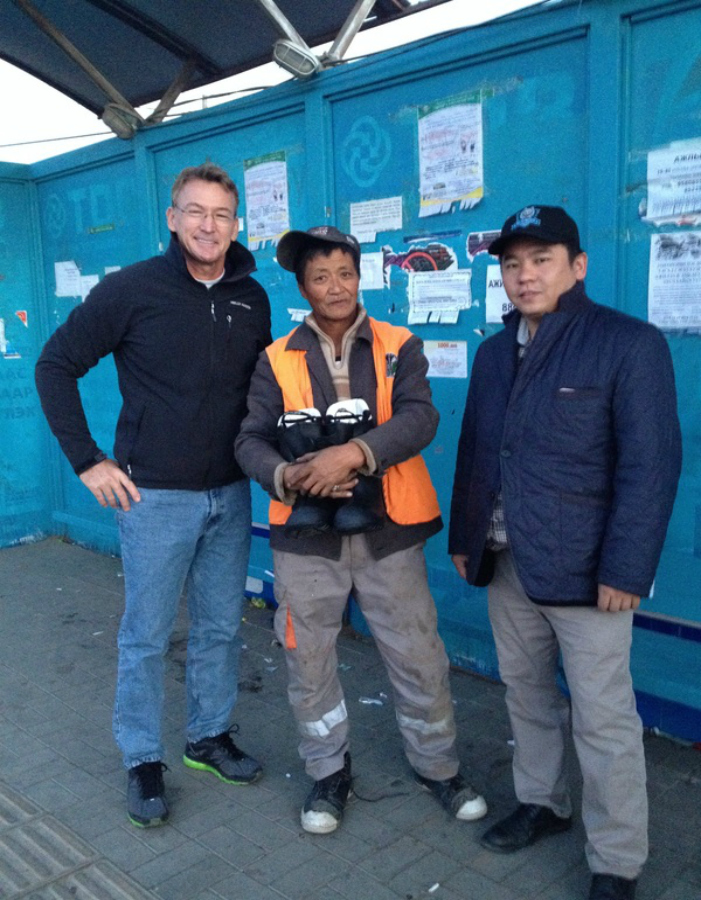 Dr. Barry (l) and Surefoot volunteer Baksaikhan (r) distribute new boots in Ulaanbaatar, Mongolia. They've just given boots to a street sweeper who works in the extreme cold every day of the year.
