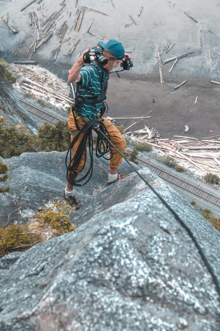 Photographer hanging on wall shooting a rock climber