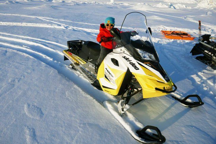 Kid riding adult sized snow machine