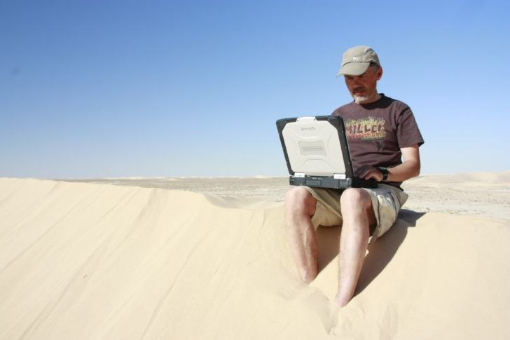 Jukka on a laptop in the sand