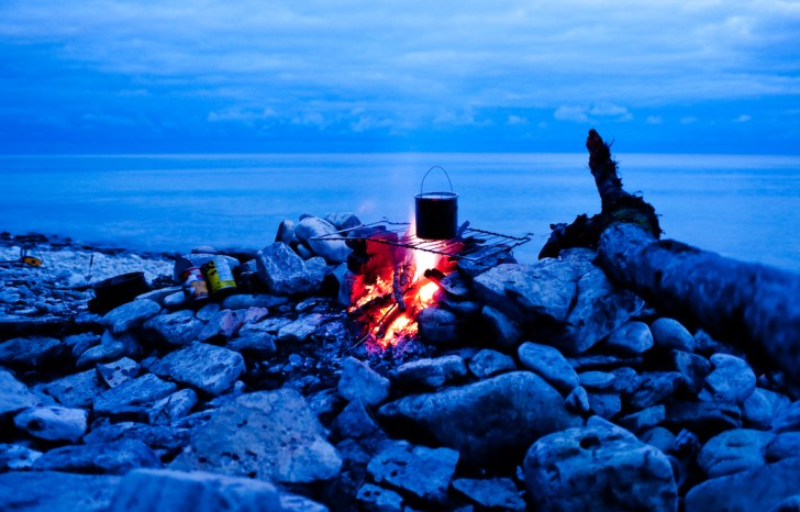 One-pot-Meals-to-Crush-the-Campfire-Glen-Harris-pot-on-fire-on-beach-night