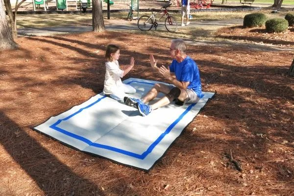grandfather and granddaughter at park sitting on outdoor recycled plastic Mountain Mat