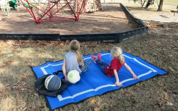 2 kids sitting on recycled plastic outdoor playmat at playground