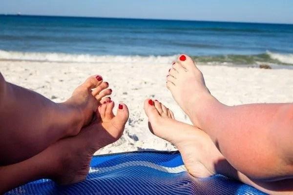 feet on beach mat facing ocean