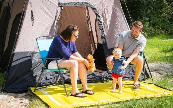 couple and baby in front of camping tent on yellow Mountain Mat