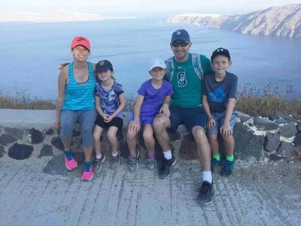 family of 2 adults and 3 kids sitting on path in Santorini