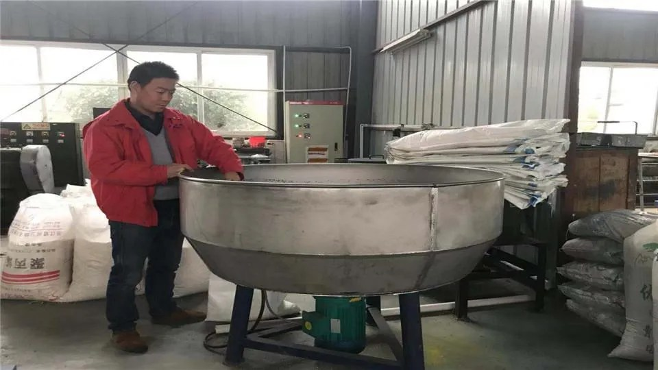 man at a big mixing pot of polypropylene granules