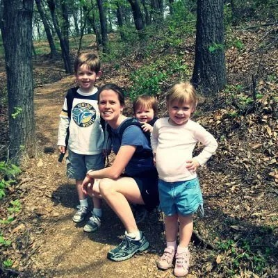 a mother and three young children posing on a hiking trail together