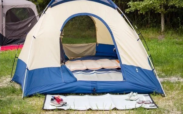 tent with camping mat in front with pair of shoes on it