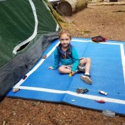 toddler on a blue camping mat