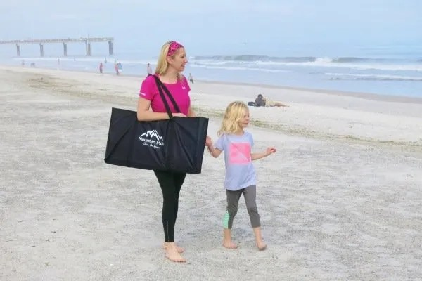 mother and child walking on beach carrying a Mountain Mat bag