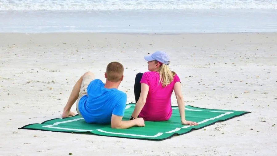 couple lying at beach on green Mountain Mat recycled plastic beach mat