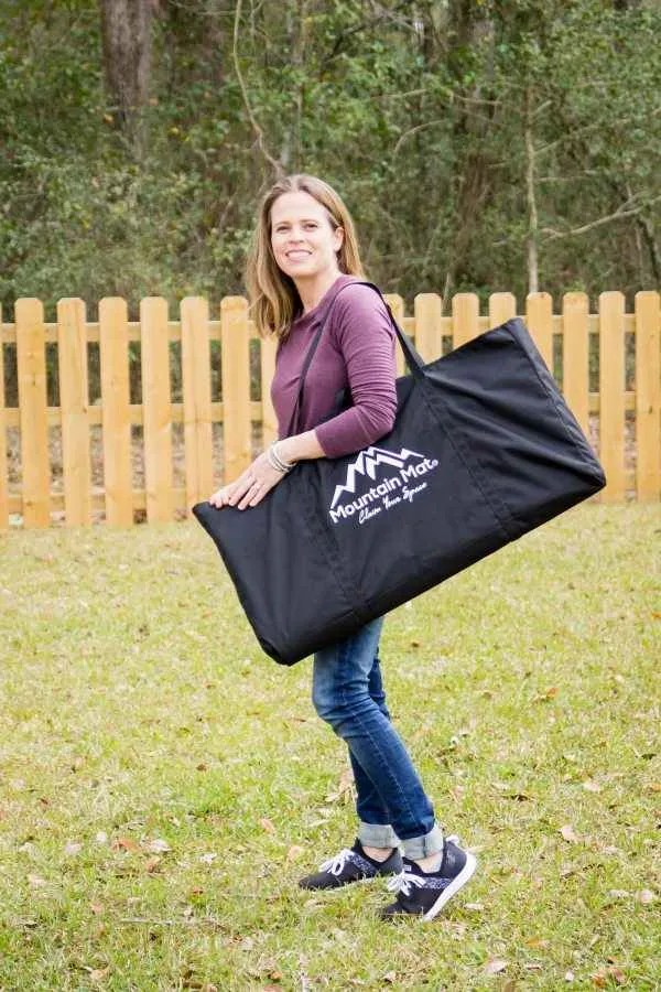 woman standing and holding a Mountain Mat carry bag