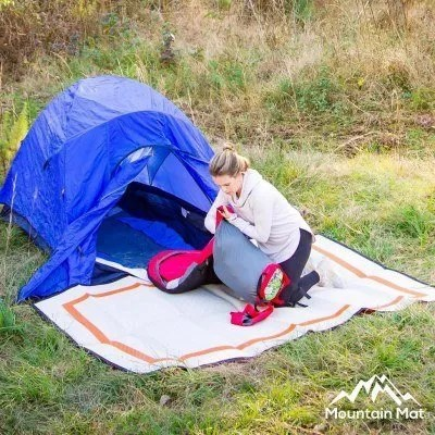 woman in front of blue tent sitting on orange and white camping mat
