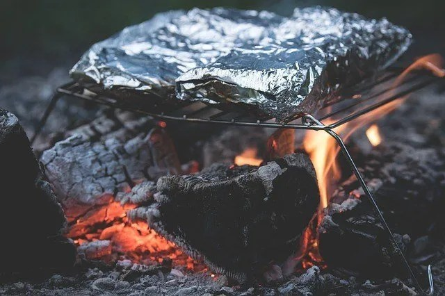 foil wrapped meal over campfire