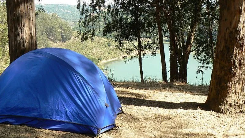 blue tent overlooking a mountain lake
