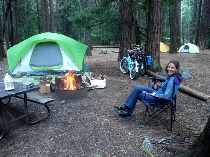 woman sitting by a campfire by a tent