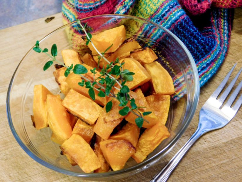 Baked butternut squash in a clear bowl with a fork.