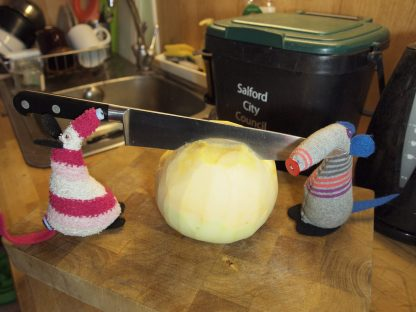 Dim and Matilda wield a big kitchen knife to cut into the whole swede.