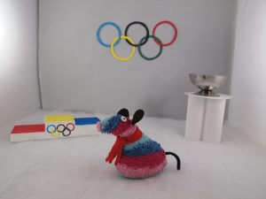 Ratvaark stands in an Olympic arena with a podium and unlit fire cauldron