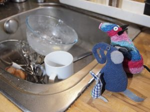 The vaarks look at a sink full of washing up.