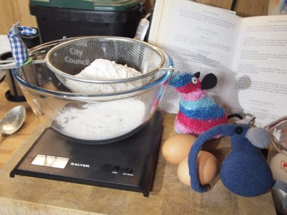 Microvaark, Ratvaark and Ernest measure out a bowl of flour