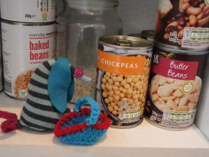 Ofelia, with her crochet shopping basket, is looking at tins of chickpeas and beans in a cupboard