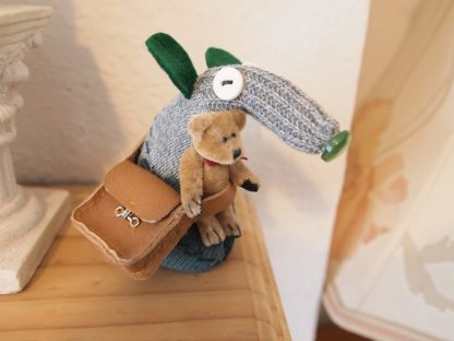 Mo has the teddy bear tucked into the strap of his satchel