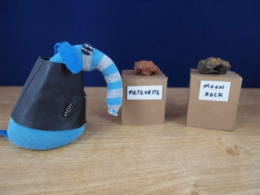 Arnold looks at some unusual rocks on plinths, labelled moon rock and meteorite