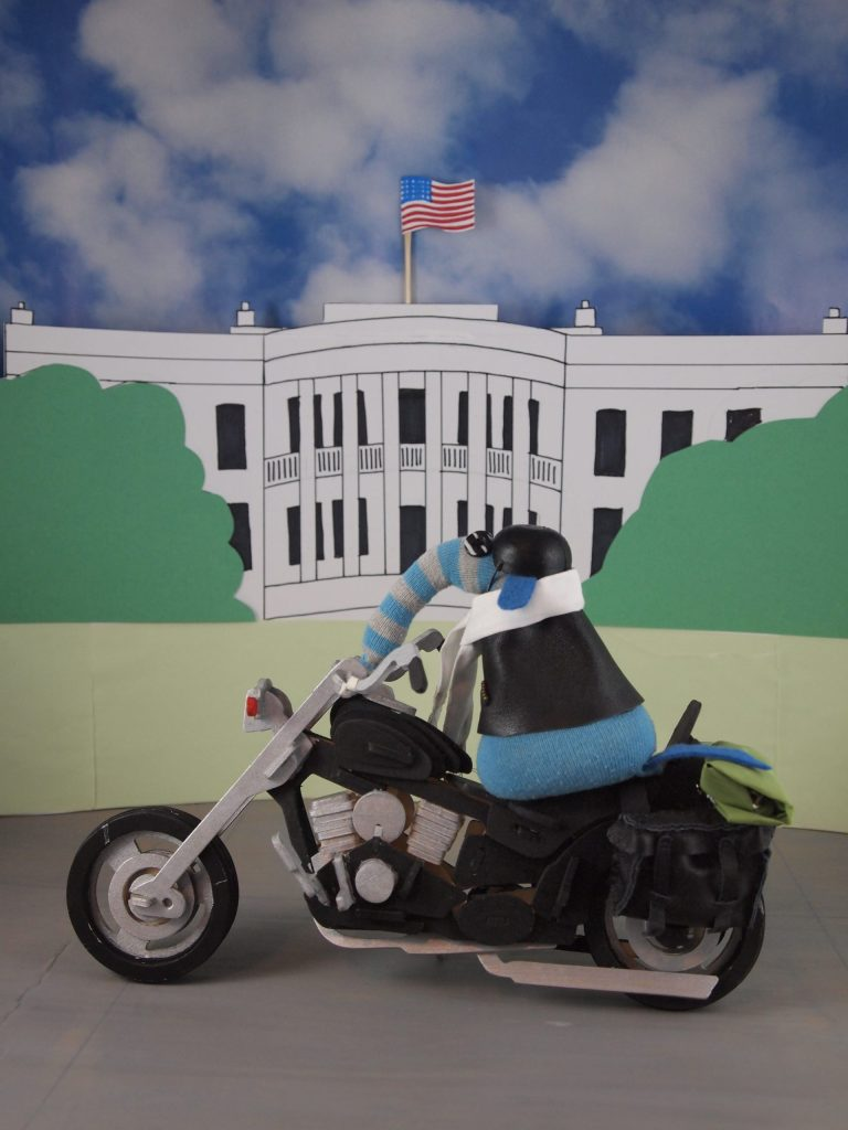 Arnold is on his motorbike, and in the background is the White House