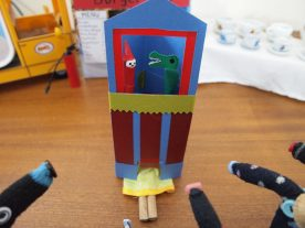 A close up of the punch and Judy shows Peggy's legs sticking out under the booth.