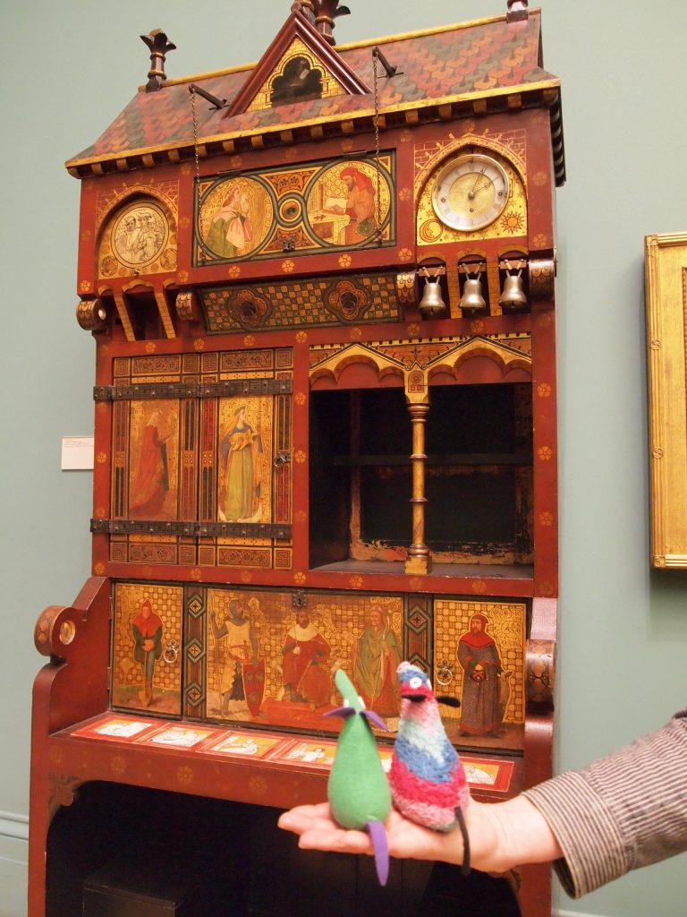They look at a very ornate cabinet with doors and cubby holes in it