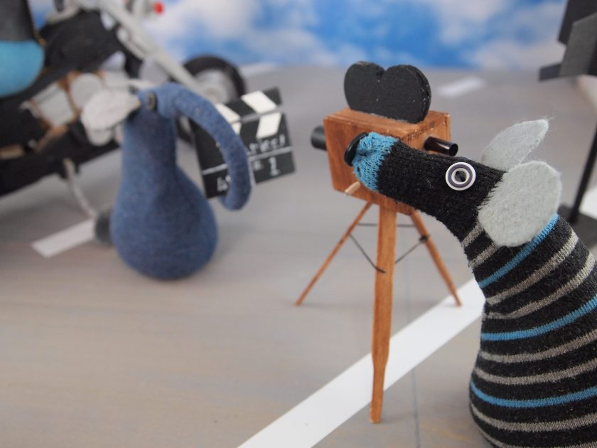 The camera vaark looks through the lens as the clapperboy vaark holds the clapperboard