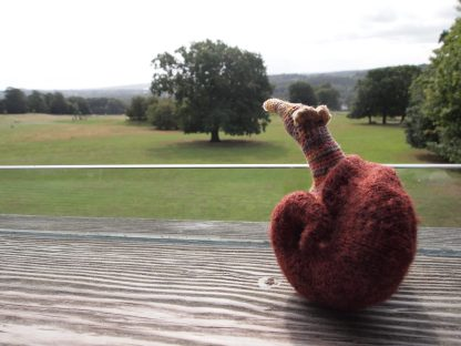 Esther looks out from a balcony over a parkland scene with trees