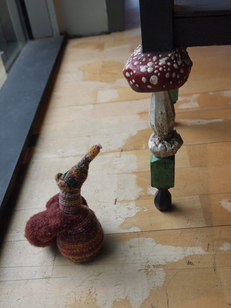 Esther looks at a table leg, carved to look like a toadstool