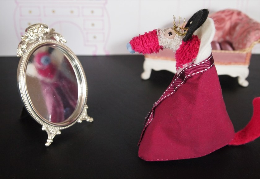 The queen looks into an ornate mirror