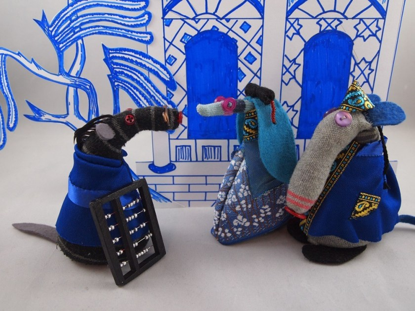 Dim is dressed as a Chinese Mandarin. Ofelia is a princess, and Bernard in a plain tunic is the clerk. They stand in front of a pagoda from the willow pattern plate. All the outfits are blue.