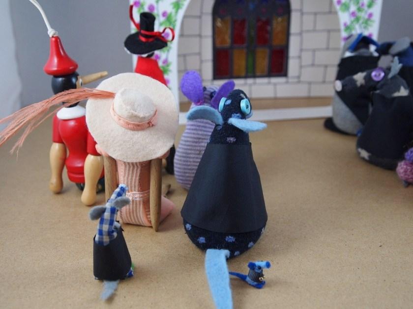 Microvaark is behind Peggy, who is wearing a hugely wide hat.