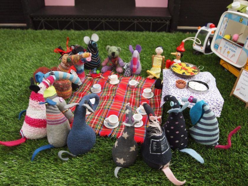 all the vaarks gather round a tartan picnic blanket with food and teacups