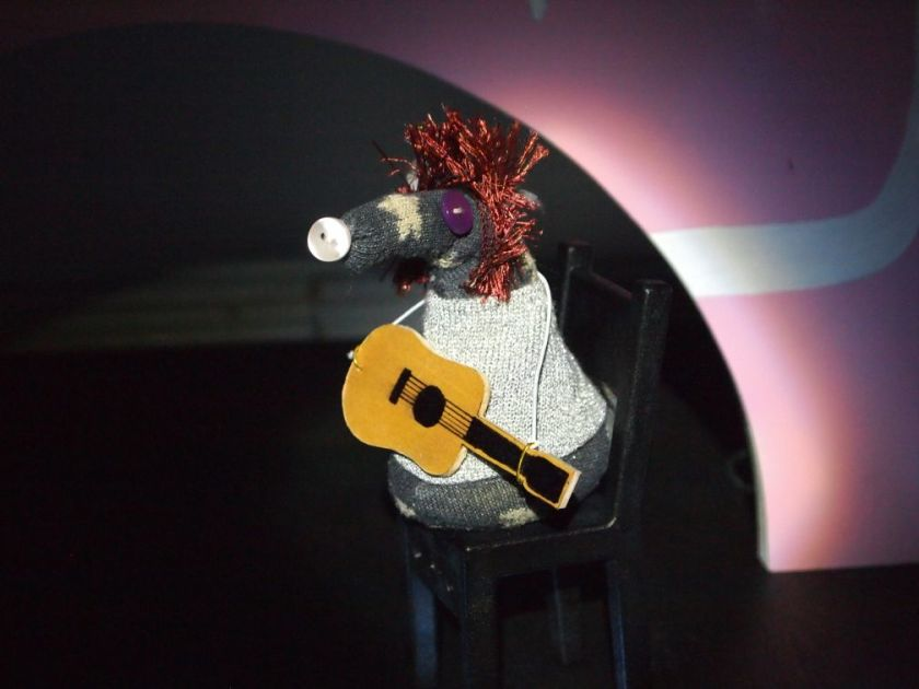 vincent as bowie with spiky hair is in the spotlight playing acoustic guitar